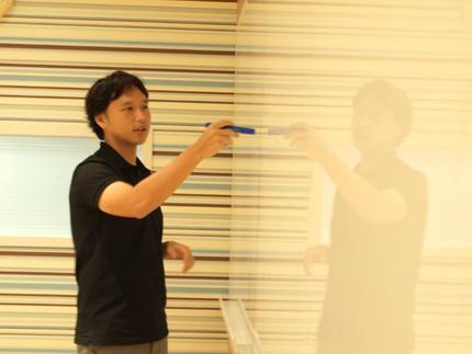 写真2 目的関数がどのような役割を担っているのか,ホワイトボードを使って取材陣に説明する吉田氏