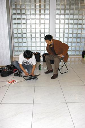 何カットか撮ってパソコンに取り込み,カメラマンさんとポースや表情の確認中(写真:編集部)