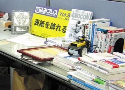 机の上には表彰状やトロフィー,そして今回の「表紙を飾れる権」のボードが飾られていました。