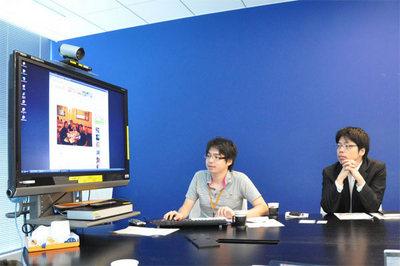 「mixiフォト」の発表デモを行う同社開発部エンジニアの井上恭輔氏(左)。右は同社代表取締役社長 笠原健治氏。井上氏は「mixiフォト」のコンセプト決定やバックエンドシステムの設計,開発から関わり,開発の初期フェーズから1年半以上となったプロジェクトを支えた。