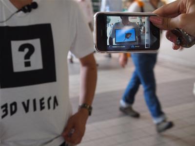 Tシャツに表示された「?」を,専用iPhoneアプリのカメラを通じて見るとさまざまな動物が映し出される。写真はサメが写っているところ