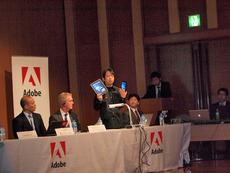 Digital Publishing Suiteのデモを行う,アドビ システムズ岩本崇氏。今回は,iPadおよびAndroid端末(Galaxy Tab)上で,ワンコンテンツマルチデバイスを実現するデモが行われた