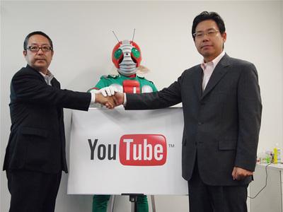 発表にあたり協力体制を誓った,YouTubeコンテンツパートナーシップ統括部長水野有平氏(右),東映株式会社折坂哲夫氏(左),仮面ライダーV3(中央)