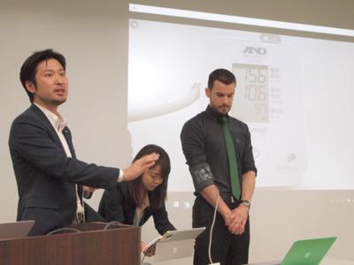 インフォテリア株式会社ネットサービス事業本部マーケティング部部長松村宗和氏(左)。発表会の最中,血圧測定をiPhoneと連携し,測定した数値をすべてデバイスに収集し,その後の分析やアドバイスにつなげる,といったシステム開発のデモを実施。ものの数分で完成した
