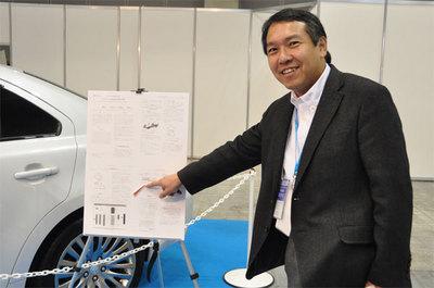 展示車の横に提示されていたスズキ自動車の技報にもTOPPERS OSの紹介が。指さしで説明しているのはTOPPERSプロジェクト会長の高田広章 名古屋大学教授。