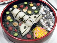 初日夜の懇親会では,ISACの名物(?)となった細工寿司が登場。左はH-IIロケットチラシ,右はスペースシャトルチラシ