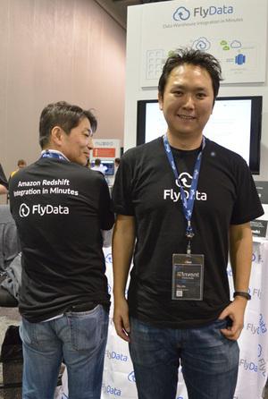 会場のFlyDataブース前でインタビューを受ける藤川幸一氏(右),同社のロゴ入りTシャツにはRedshiftのロゴも。これを許されるのは特別なパートナーだけとのこと