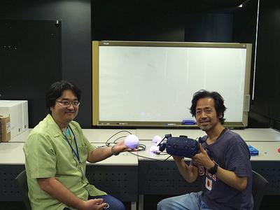 準備に忙しい中,インタビューに応じてくれたアルファコードCEO兼VRコンテンツプロデューサー 水野拓宏氏(左)と音楽座ミュージカルの俳優 広田勇二氏(右)。インタビュー場所は,アルファコードの開発スペースという,まさに臨場感のあるインタビューとなった