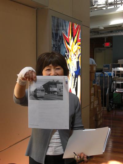 写真6:スタッフが手にしているのが,現オフィスの前身である映画館の設立当時の様子