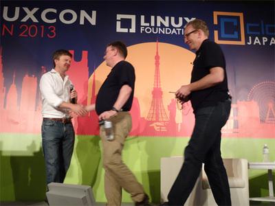 Jim Zemlin氏(左)と握手するLinus氏,右はDirk Hohndel氏
