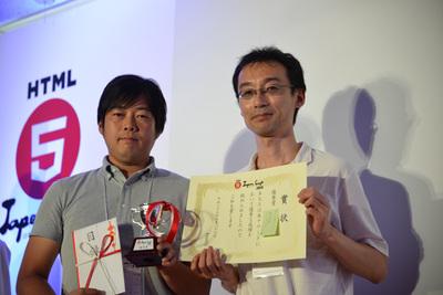 優秀賞のIMJ 西田氏(左)と,プレゼンターの審査委員,羽田野太巳氏
