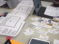 各チームで記入したシートやポストイット,カードなどを組み合わせて自分たちのアイデアを「形」にする作業が進む(右)